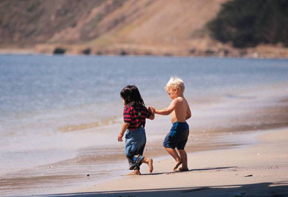Two small children walking on the beach hand in hand